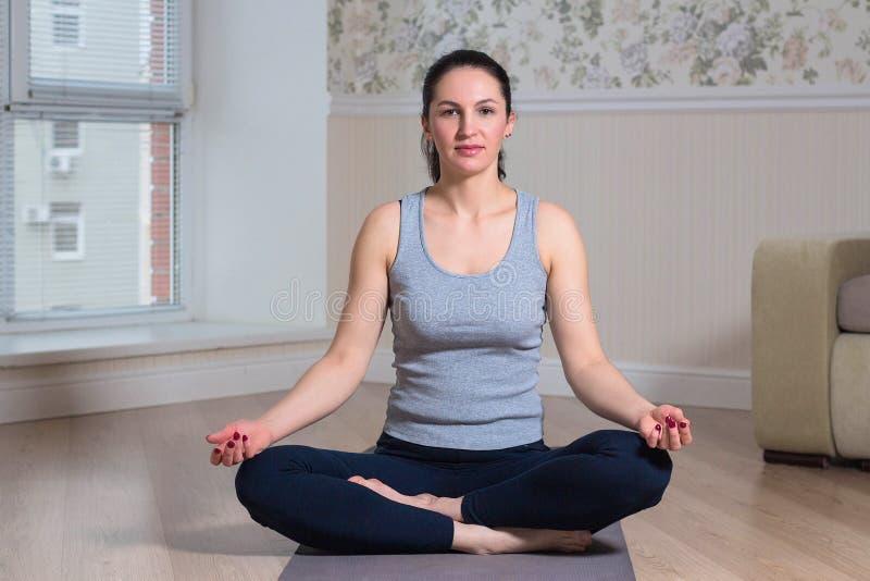 schöne junge Frau, die in der Lotoshaltung sitzt und zu Hause meditiert stockfotografie