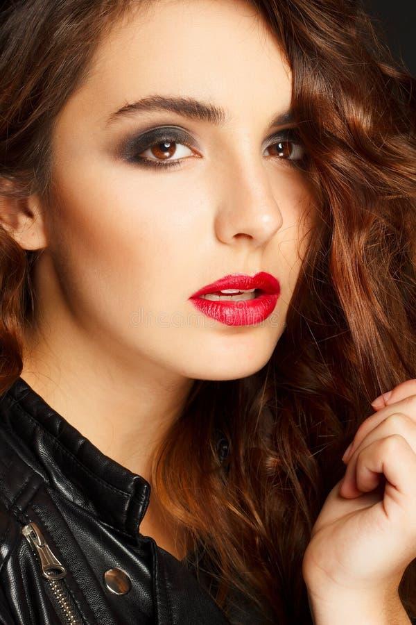 Schöne junge Frau, die in der schwarzen Lederjacke über grauem b aufwirft lizenzfreies stockfoto