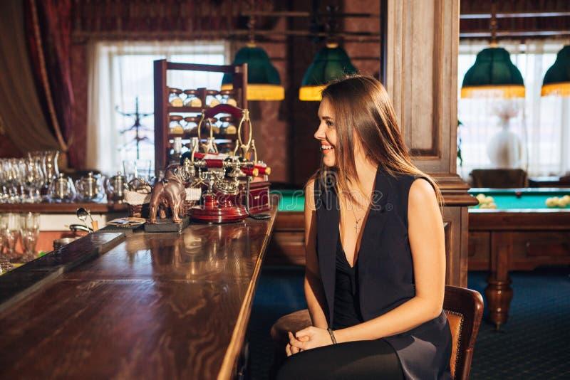 Schöne junge Frau, die an der Stange spricht mit dem Barmixer sitzt lizenzfreies stockbild
