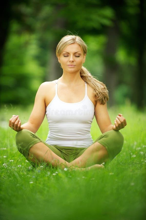 Schöne junge Frau, die in der Yogahaltung im Park sitzt stockbild