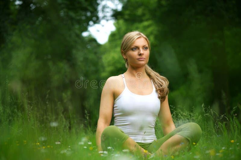 Schöne junge Frau, die in der Yogahaltung im Wald sitzt stockfotografie