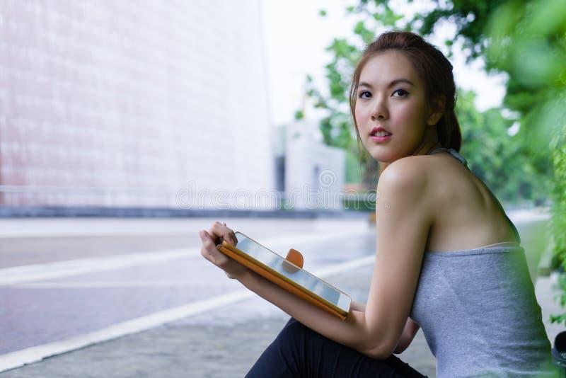 Schöne junge Frau, die digitalen Tablet-Computer in Park outd verwendet lizenzfreies stockfoto
