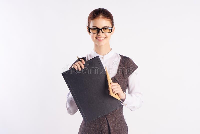 Schöne junge Frau, die Dokumente auf weißem Hintergrund, Lehrer verwahrt lizenzfreies stockfoto