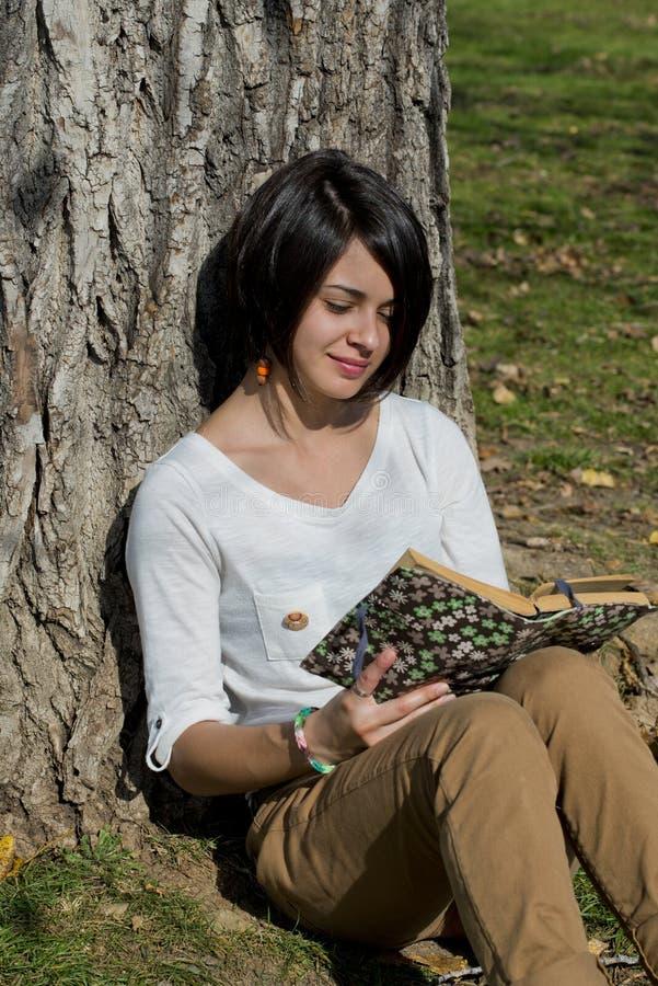 Schöne junge Frau, die draußen ein Buch liest lizenzfreie stockbilder