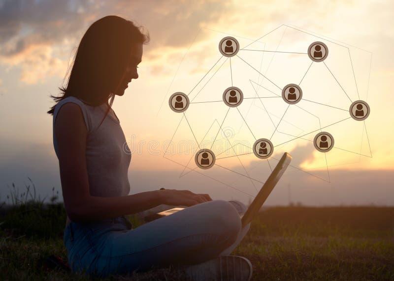 Schöne junge Frau, die draußen, unter Verwendung eines Laptops, Kommunikationskonzept sitzt stockfotografie