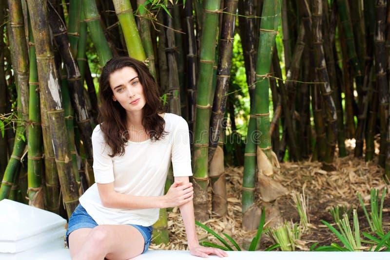 Schöne junge Frau, die durch Bambusbäume sitzt stockfotos