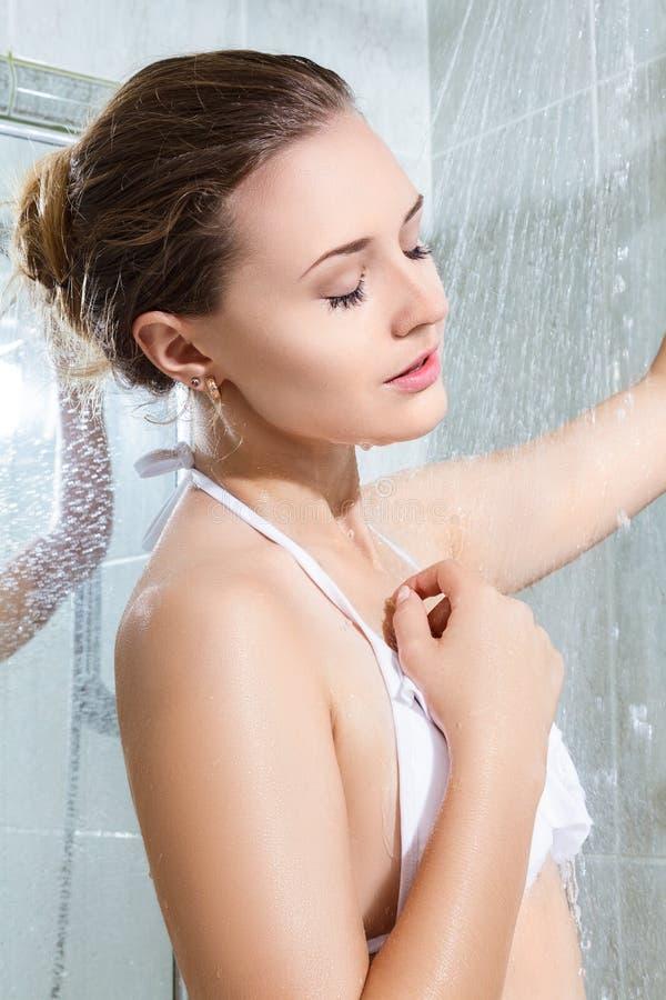 Schöne junge Frau, die Dusche nimmt stockfotografie