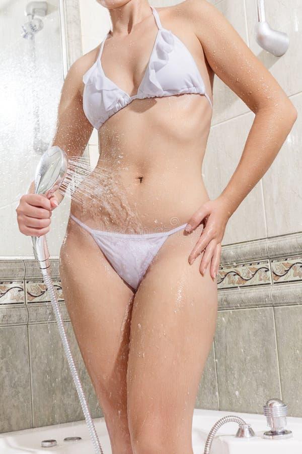 Schöne junge Frau, die Dusche nimmt stockfoto