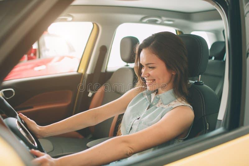Schöne junge Frau, die ein Auto an der Verkaufsstelle kauft Weibliches Modellsitzen sitzt im Autoinnenraum lizenzfreie stockbilder