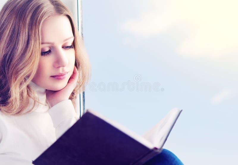 Schöne junge Frau, die ein Buch beim Sitzen an einem Fenster liest lizenzfreie stockbilder