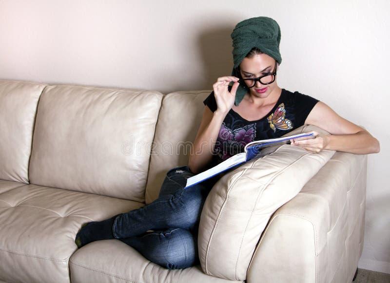 Schöne junge Frau, die ein Buch liest stockbild