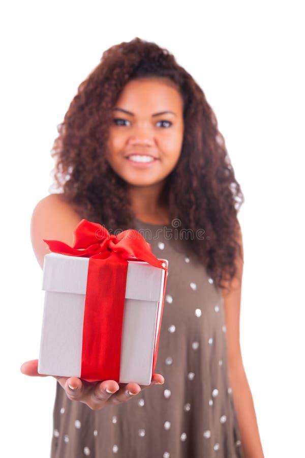 Schöne junge Frau, die ein Geschenk über einem weißen Hintergrund hält lizenzfreie stockfotos