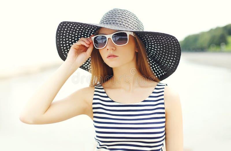Schöne junge Frau, die ein gestreiftes Kleid, einen schwarzen Strohhut und eine Sonnenbrille trägt stockfotos