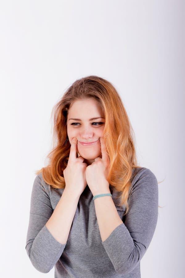 Schöne junge Frau, die ein Lächeln, ihre Finger nahe halten zwingt stockbild