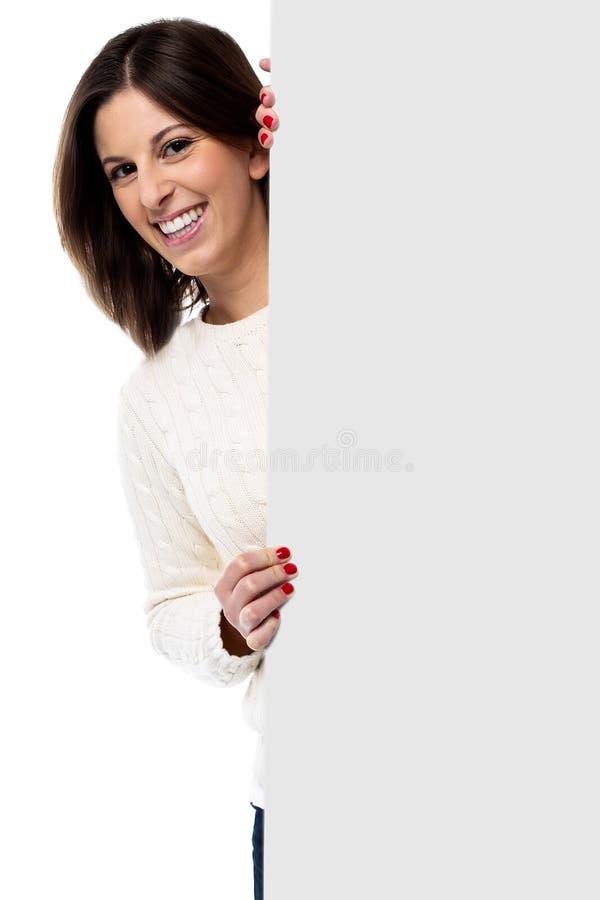 Schöne junge Frau, die ein leeres Zeichen hält lizenzfreie stockfotografie