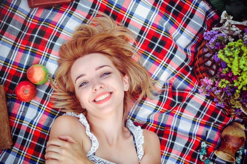 Schöne junge Frau, die ein Picknick in der Landschaft hat Glücklicher gemütlicher Tag draußen geöffnet Eine lächelnde Frau liegt  stockfotografie