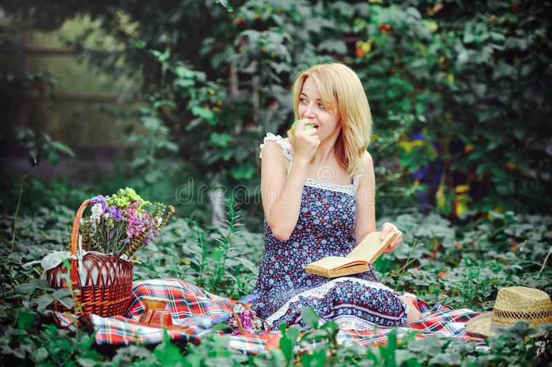 Schöne junge Frau, die ein Picknick in der Landschaft hat Glücklicher gemütlicher Tag draußen geöffnet Lächelnde Frau, die den Ap stockbild