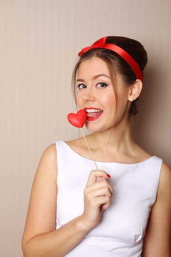 Schöne junge Frau, die ein rotes Inneres anhält lizenzfreie stockfotografie