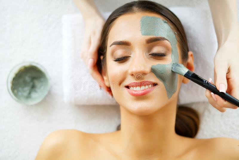 Schöne junge Frau, die eine Gesichts-Behandlung am Schönheits-Salon erhält Haut und Sorgfalt Schönheit, die mit Gesichtsmaske lie lizenzfreie stockbilder