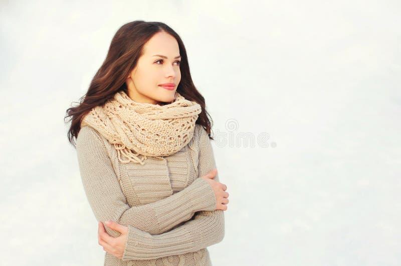 Schöne junge Frau, die eine gestrickte Strickjacke und einen Schal im Winter trägt stockfoto