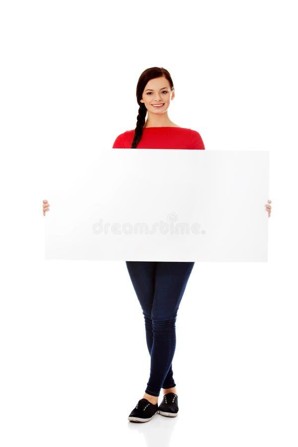 Schöne junge Frau, die eine leere Fahne hält lizenzfreies stockfoto