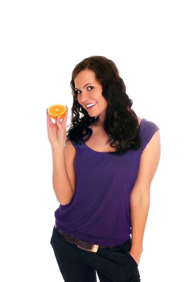 Schöne junge Frau, die eine Orange anhält lizenzfreies stockfoto