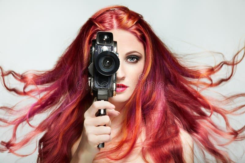 Schöne junge Frau, die eine Retro- Videokamera verwendet lizenzfreie stockfotos