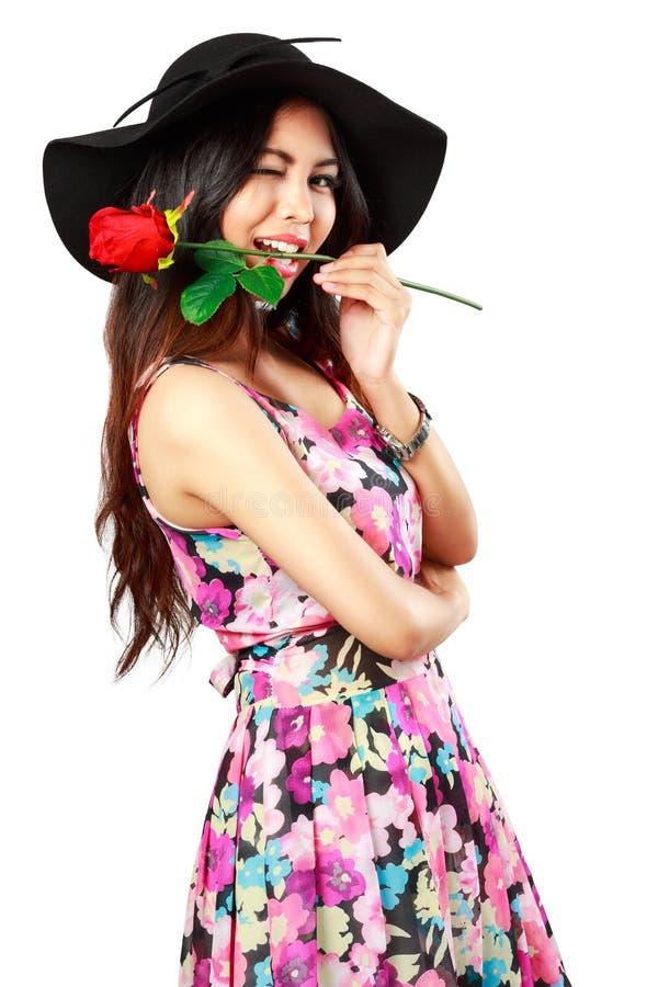 Schöne junge Frau, die eine rote Rose hält lizenzfreie stockbilder