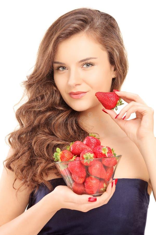 Schöne junge Frau, die eine Schüssel Erdbeeren hält lizenzfreies stockbild