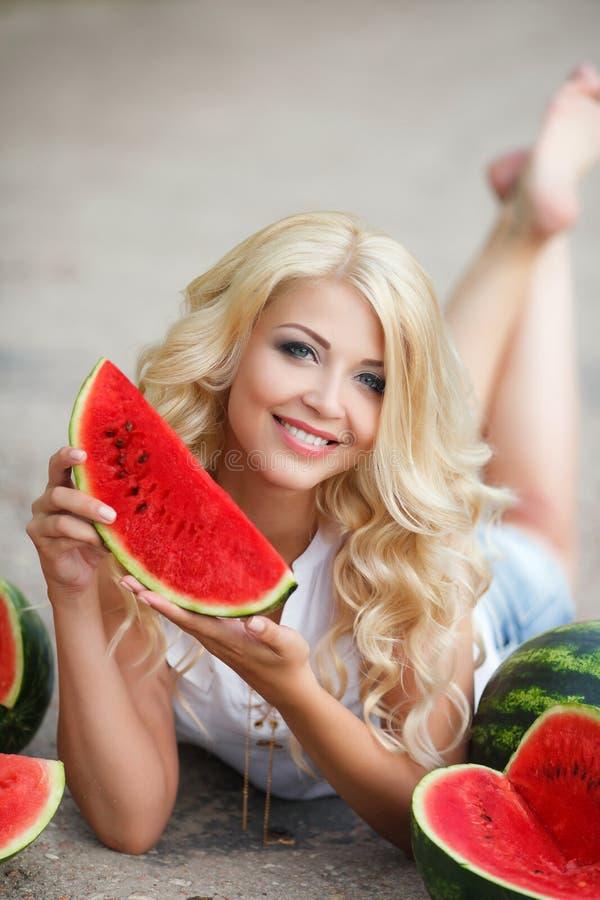 Schöne junge Frau, die eine Scheibe der reifen Wassermelone hält lizenzfreies stockfoto