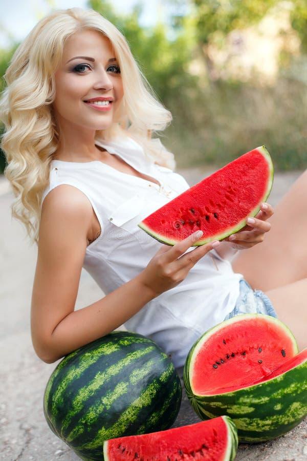 Schöne junge Frau, die eine Scheibe der reifen Wassermelone hält lizenzfreies stockbild