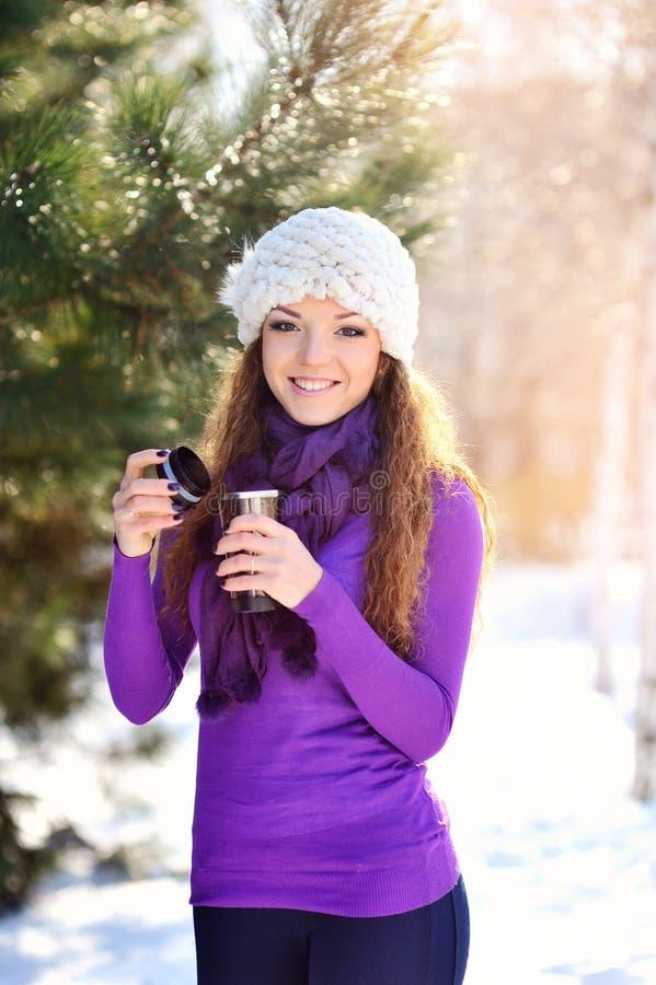Schöne junge Frau, die eine Tasse Tee in der Wintersonne isst stockfoto