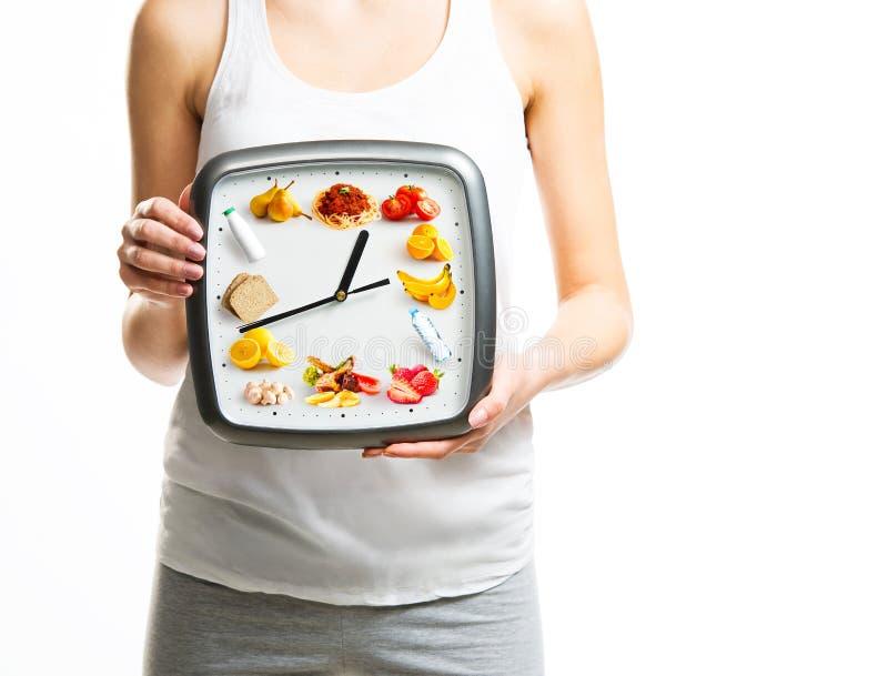 Schöne junge Frau, die eine Uhr mit Lebensmittel hält stockfoto