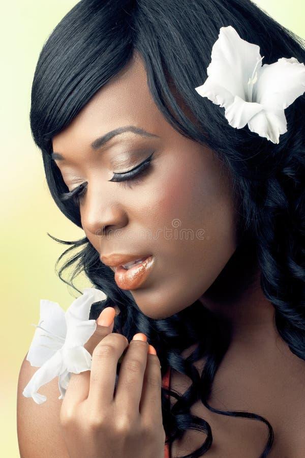 Schöne junge Frau, die eine weiße Blume anhält lizenzfreie stockfotografie
