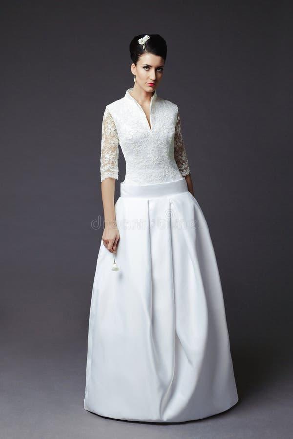 Schöne junge Frau, die in einem Hochzeitskleid aufwirft lizenzfreies stockfoto