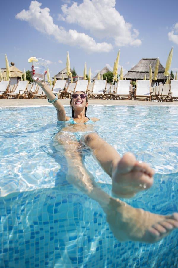 Schöne junge Frau, die in einem Swimmingpool etwas trinken möchte stockfoto