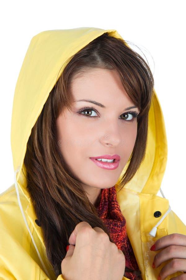 Schöne junge Frau, die einen gelben Regenmantel trägt lizenzfreies stockfoto