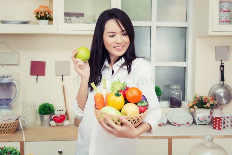 Schöne junge Frau, die einen gesunden grünen Apfel im kitche isst lizenzfreies stockbild