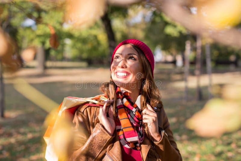 Schöne junge Frau, die in einen Park im Herbst nach dem Einkauf geht stockfotos