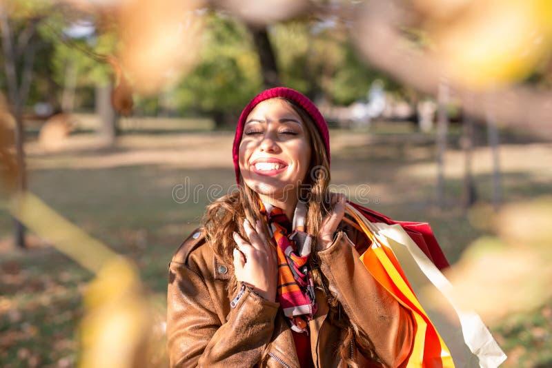 Schöne junge Frau, die in einen Park im Herbst nach dem Einkauf geht lizenzfreie stockbilder