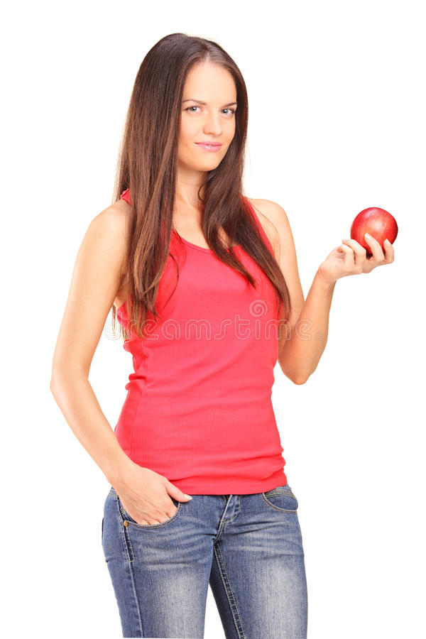 Schöne junge Frau, die einen roten Apfel anhält lizenzfreie stockfotos