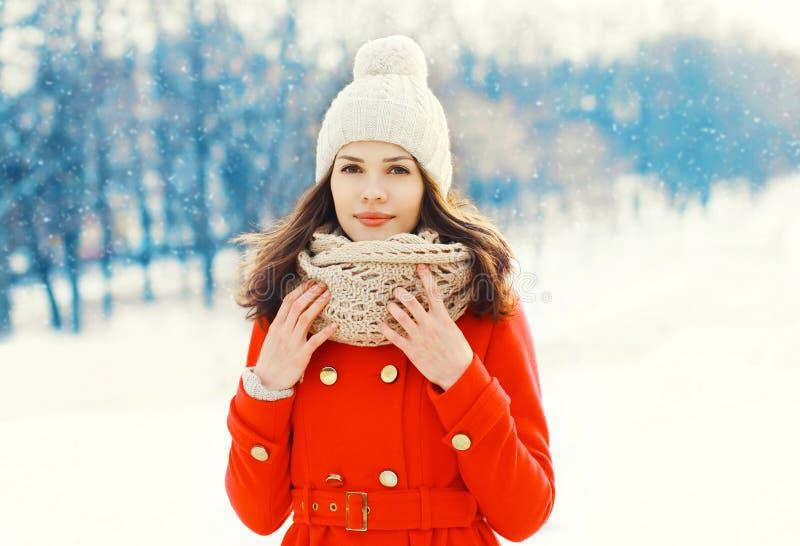 Schöne junge Frau, die einen roten coa trägt stockfotos