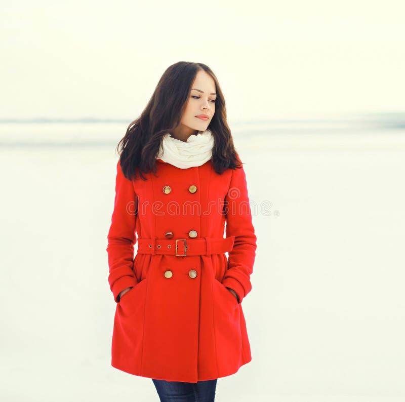 Schöne junge Frau, die einen roten Mantel trägt lizenzfreie stockbilder
