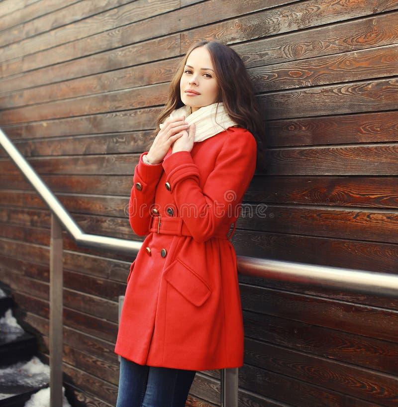 Schöne junge Frau, die einen roten Mantel und einen Schal trägt stockfotos