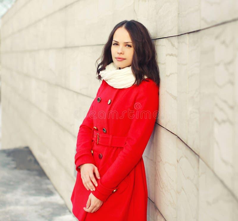 Schöne junge Frau, die einen roten Mantel und einen Schal trägt stockbilder