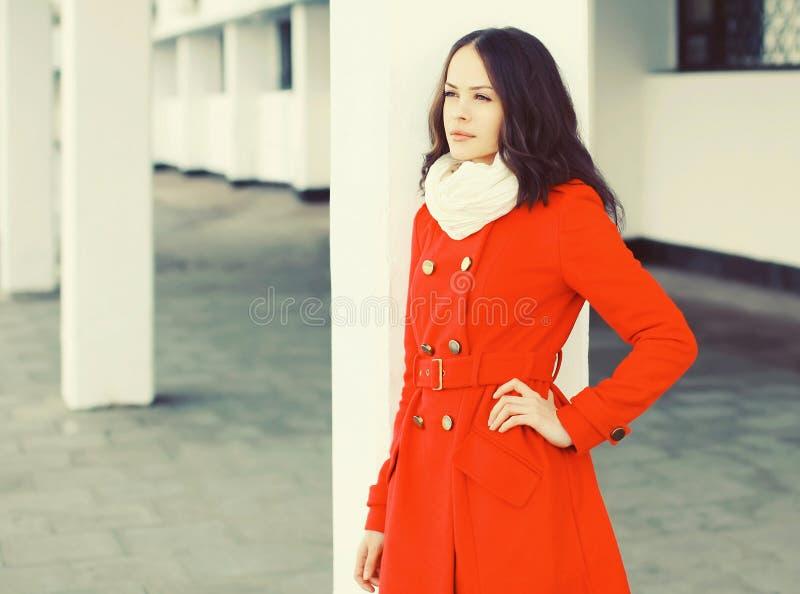 Schöne junge Frau, die einen roten Mantel und einen Schal trägt stockbild