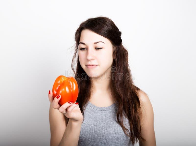 Schöne junge Frau, die einen roten Pfeffer isst gesundes Lebensmittel - starkes Zahnkonzept stockfoto