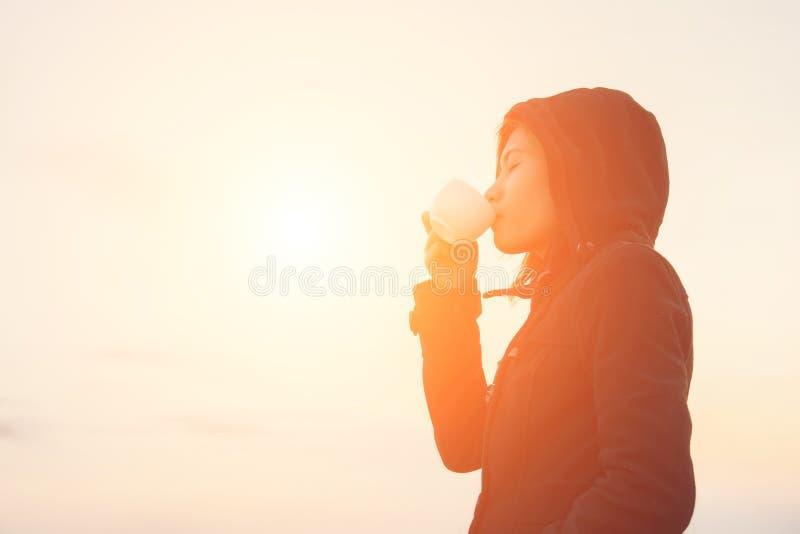 Schöne junge Frau, die einen Tasse Kaffee mit Sonnenaufgang in t trinkt lizenzfreie stockbilder