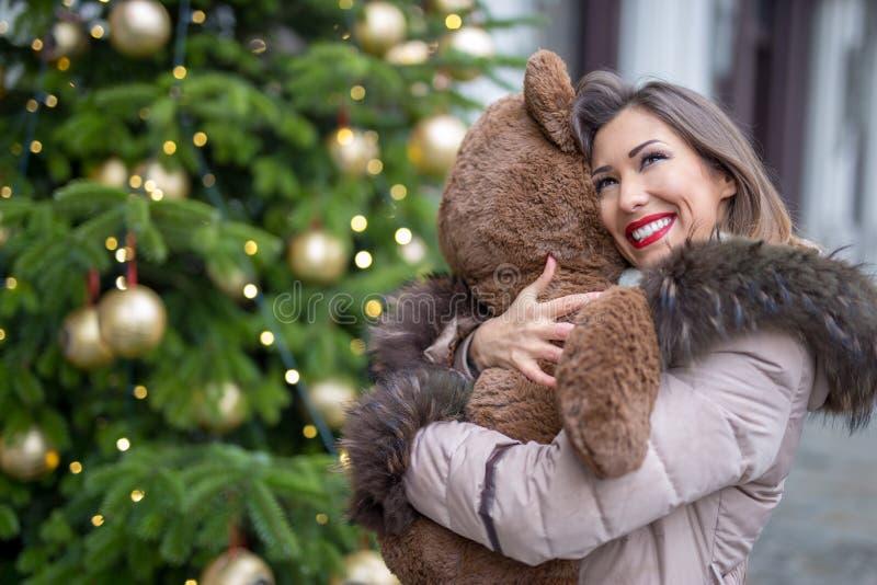 Schöne junge Frau, die einen Teddybären anwesend für Weihnachten umarmt stockbilder
