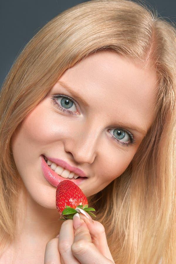 Schöne junge Frau, die Erdbeere isst stockfotos